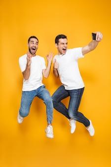 Comprimento total de dois amigos homens alegres e animados, vestindo camisetas em branco, pulando isolados sobre a parede amarela, tirando uma selfie