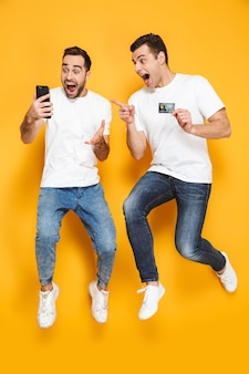 Comprimento total de dois amigos homens alegres e animados, vestindo camisetas em branco, pulando isolados sobre uma parede amarela, olhando para o celular, celebrando o sucesso