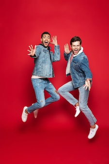 Comprimento total de dois amigos jovens animados usando jaquetas jeans isoladas sobre uma parede vermelha, pulando