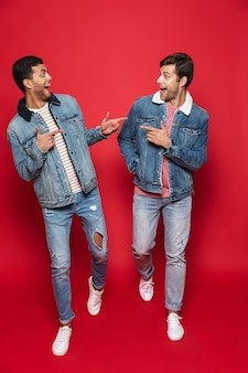 Comprimento total de dois entusiasmados amigos jovens vestindo jaquetas jeans isoladas sobre uma parede vermelha, caminhando, conversando