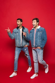 Comprimento total de dois jovens sorridentes caminhando isolados sobre uma parede vermelha, conversando