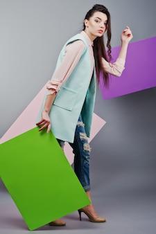 Comprimento total de menina bonita, com placa de publicidade em branco verde, sobre fundo cinza e banner rosa e violeta
