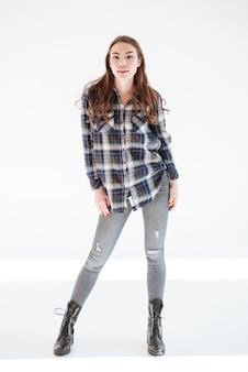 Comprimento total de mulher atraente em jeans e camisa xadrez