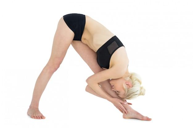 Comprimento total de mulher desportiva, curvando-se para a perna