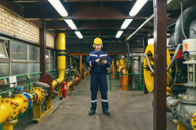 Comprimento total de trabalhador caucasiano em traje de proteção, capacete e antifones nas orelhas usando o tablet para o trabalho em pé na planta da indústria pesada.