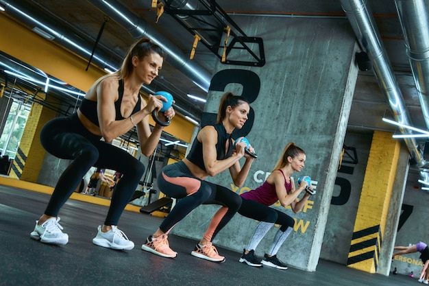 Comprimento total de três jovens garotas de fitness forte, exercitando-se com kettlebells de ferro na academia, fazendo exercícios de crossfit. pessoas esportivas e conceito de musculação
