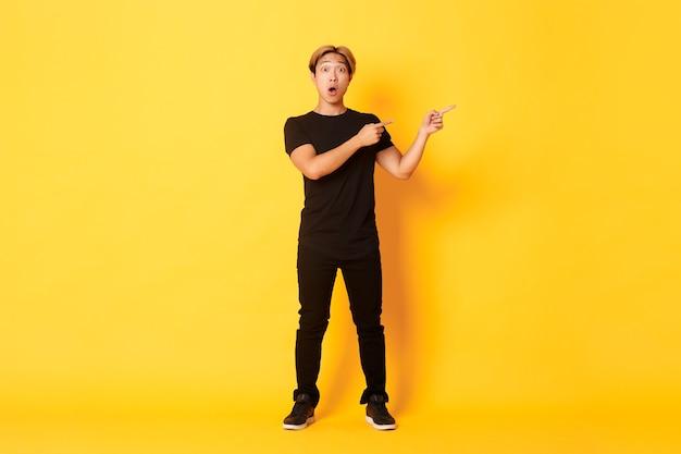 Comprimento total de um cara asiático atraente surpreso e impressionado apontando os dedos no canto superior direito, mostrando o logotipo, parede amarela