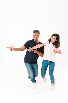 Comprimento total de um casal alegre e atraente, vestindo roupa casual, em pé, isolado na parede branca, apontando para o lado oposto