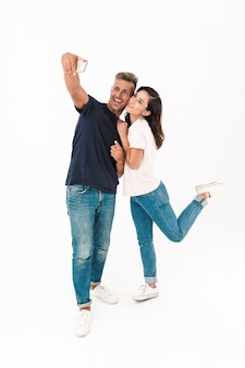Comprimento total de um casal alegre e atraente, vestindo roupa casual, em pé, isolado na parede branca, tirando uma selfie