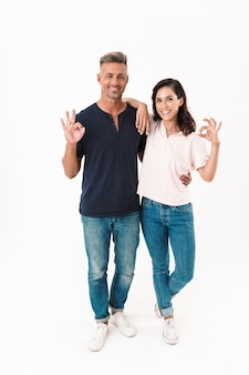 Comprimento total de um casal alegre e atraente, vestindo roupa casual, em pé, isolado sobre uma parede branca, mostrando-se bem