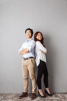 Comprimento total de um casal asiático alegre, de costas um para o outro