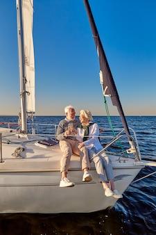 Comprimento total de um casal feliz da família sênior bebendo vinho ou champanhe enquanto celebra o casamento