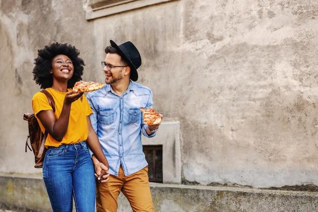 Comprimento total de um casal feliz multirracial caminhando ao ar livre, de mãos dadas e comendo pizza