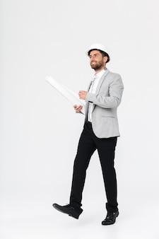 Comprimento total de um construtor de homem barbudo confiante vestindo terno e capacete de segurança em pé isolado sobre uma parede branca, carregando plantas