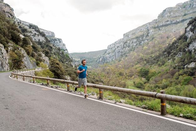 Comprimento total de um esportista solitário correndo na estrada pavimentada da montanha com cerca contra o vale