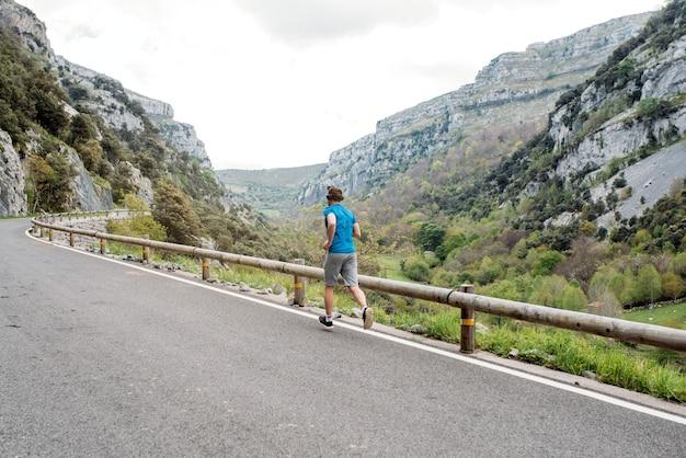 Comprimento total de um esportista solitário irreconhecível correndo na estrada pavimentada da montanha com uma cerca contra o vale