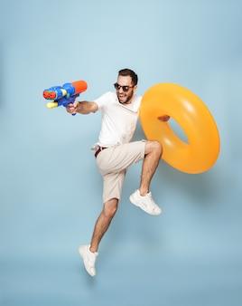 Comprimento total de um homem alegre e animado vestindo uma camiseta em branco, pulando isolado na parede azul, se divertindo com um anel inflável e uma pistola d'água