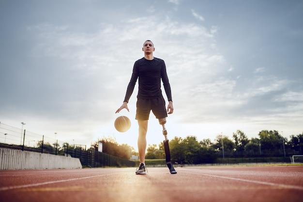 Comprimento total de um homem deficiente caucasiano desportivo em roupas esportivas e perna artificial dribla a bola em pé na pista de corrida.