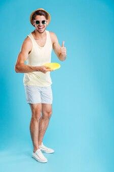 Comprimento total de um jovem alegre jogando disco frisbee e mostrando os polegares para cima sobre a parede azul