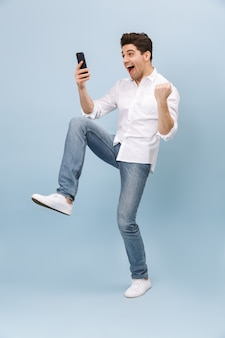 Comprimento total de um jovem bonito e alegre isolado em um azul, segurando um telefone celular, comemorando
