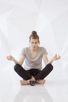 Comprimento total de um jovem meditando em posição de lótus sobre um fundo branco de polígono
