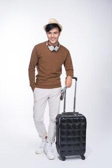 Comprimento total de um jovem turista asiático segurando o passaporte com uma mala sobre fundo cinza