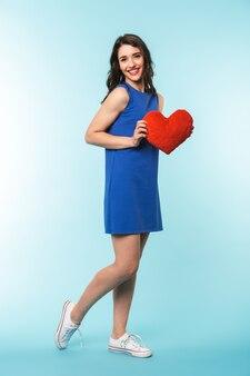 Comprimento total de uma alegre jovem morena de pé sobre o fundo azul, segurando um coração vermelho