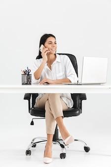 Comprimento total de uma atraente jovem empresária sentado na mesa, isolado na parede branca, falando no celular
