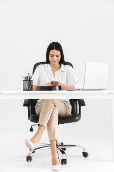 Comprimento total de uma atraente jovem empresária sentado na mesa, isolado sobre uma parede branca, usando telefone celular