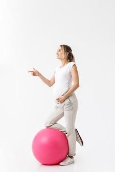 Comprimento total de uma bela jovem grávida fazendo exercícios de esporte com uma bola de fitness isolada sobre um fundo branco, apontando para longe