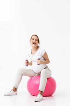 Comprimento total de uma bela jovem grávida fazendo exercícios de esporte com uma bola de fitness isolada sobre um fundo branco, segurando halteres