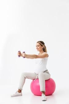 Comprimento total de uma bela jovem grávida fazendo exercícios de esporte com uma bola de fitness isolada sobre um fundo branco