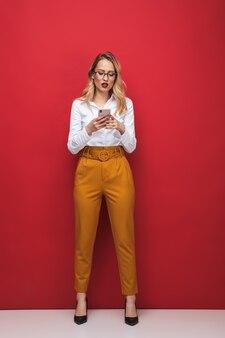 Comprimento total de uma bela jovem loira em estado de choque, isolada sobre um fundo vermelho, segurando um telefone celular