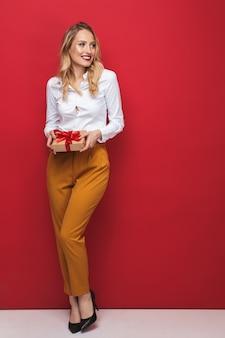 Comprimento total de uma bela jovem loira em pé isolado sobre um fundo vermelho, segurando uma caixa de presente