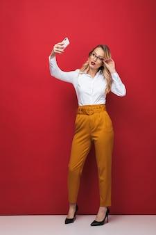 Comprimento total de uma bela jovem loira em pé isolado sobre um fundo vermelho, tirando uma selfie
