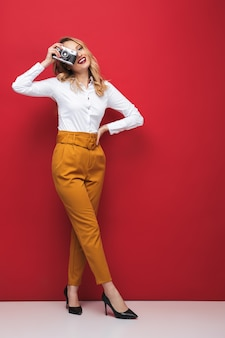 Comprimento total de uma bela jovem loira em pé sobre um fundo vermelho, segurando uma câmera fotográfica