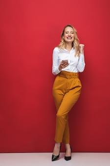 Comprimento total de uma bela jovem loira feliz em pé isolado sobre um fundo vermelho, segurando um telefone celular, comemorando o sucesso