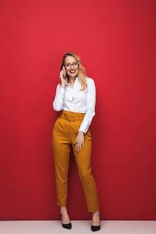 Comprimento total de uma bela jovem loira feliz em pé isolado sobre um fundo vermelho, segurando um telefone celular