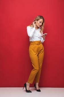 Comprimento total de uma bela jovem loira pensativa, isolada sobre um fundo vermelho, segurando um telefone celular