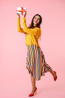 Comprimento total de uma bela jovem vestindo roupas coloridas, em pé isolado sobre a rosa, segurando uma caixa de presente