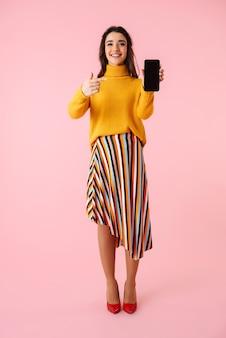 Comprimento total de uma bela jovem vestindo roupas coloridas em pé isolado sobre o rosa, mostrando uma tela em branco do celular