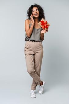 Comprimento total de uma feliz jovem africana vestida casualmente, isolada, falando no celular, mostrando a caixa de presente
