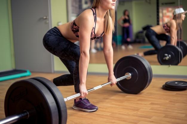 Comprimento total de uma forma jovem malhando com um barbell na academia. fêmea de fisiculturista exercitando na academia.