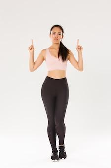 Comprimento total de uma garota fitness não divertida e cética, atleta asiática em roupas esportivas, reclamando, emburrada, descontente e apontando o dedo para cima