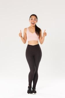 Comprimento total de uma garota fitness sorridente, espantada e satisfeita, atleta feminina em uso ativo, gostando de nova academia ou programa de treino, mostrando o polegar para cima satisfeita.