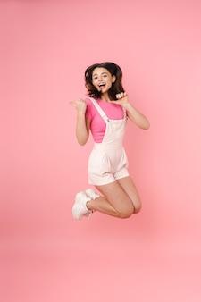 Comprimento total de uma jovem adolescente muito animada pulando isolada, se divertindo, apontando para longe
