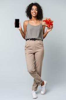 Comprimento total de uma jovem africana feliz, vestida casualmente, de pé, isolada, segurando um celular de tela em branco, mostrando uma caixa de presente