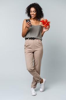 Comprimento total de uma jovem africana feliz, vestida casualmente, de pé, isolada, usando um telefone celular, mostrando uma caixa de presente