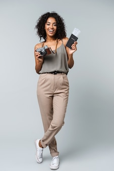 Comprimento total de uma jovem africana feliz, vestida casualmente, isolada, segurando uma câmera fotográfica, mostrando o passaporte com as passagens aéreas