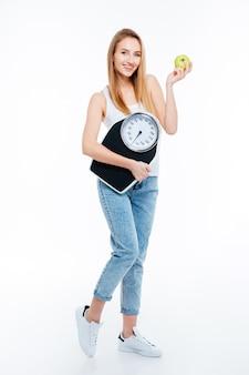 Comprimento total de uma jovem atraente e feliz em pé e segurando uma balança e maçã verde sobre fundo branco